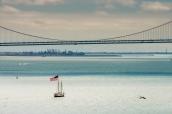 Le drapeau américain flotte sur un bateau se dirigeant vers Bay Bridge, San Francisco