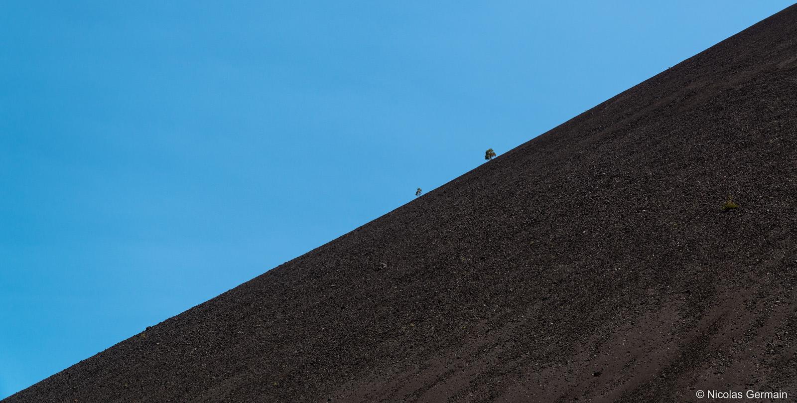 De rares arbres parviennent à pousser sur la pente rocailleuse de Cinder Cone, Lassen Volcanic