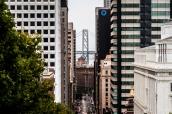 Rue pentue et buildings du quartier de Financial District à San Francisco laissant apparaître dans le fond le Bay Bridge