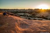 Un randonneur apprécie le coucher de soleil sur Elephant Hill et les aiguilles de Chesler Park dans Canyonlands
