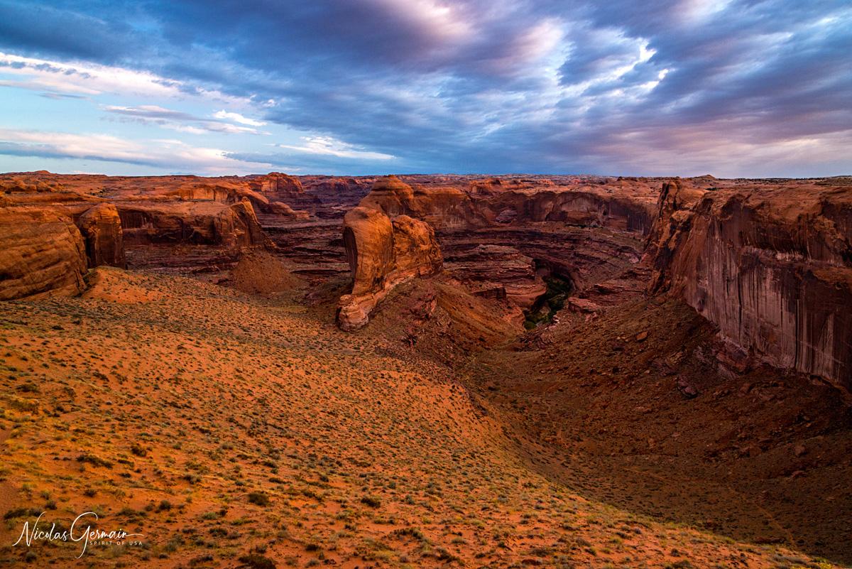 Lever de soleil nuageux sur Coyote Gulch et Stevens Arch vus de Crack-in-the-Wall